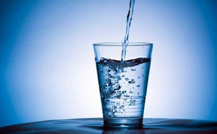Vann som helles opp i et glass