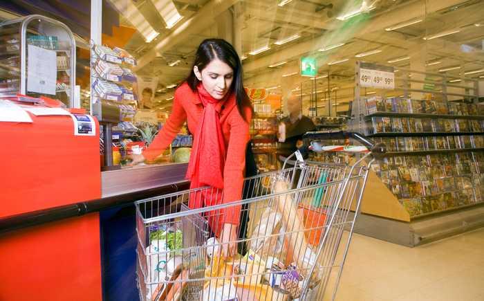 Kvinne som legger varer på båndet i kassen i en butikk.