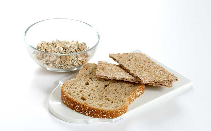 Grovbrød og knekkebrød ligger på et fat. I bakgrunnen står en bolle med kornblanding.
