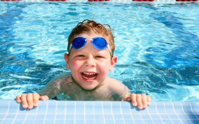 Liten, blid gutt i basseng.