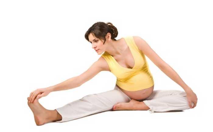 Gravid kvinne som strekker ut etter trening.