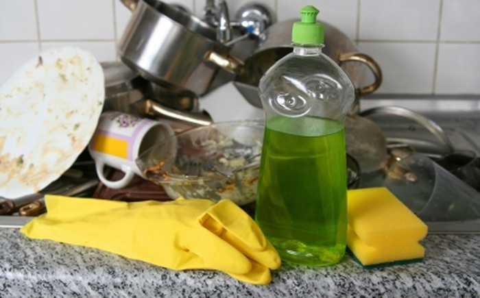 En haug med skitten oppvask på en kjøkkenbenk.