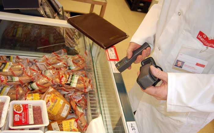 En inspektør fra Mattilsynet inspiserer en kjøttdisk i en dagligvarebutikk