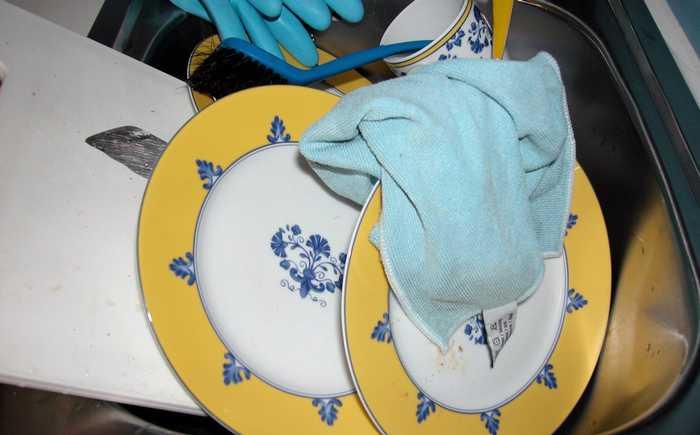 En kjøkkenklut ligger i oppvaskkummen sammen med tallerkener, kopp og fjøl