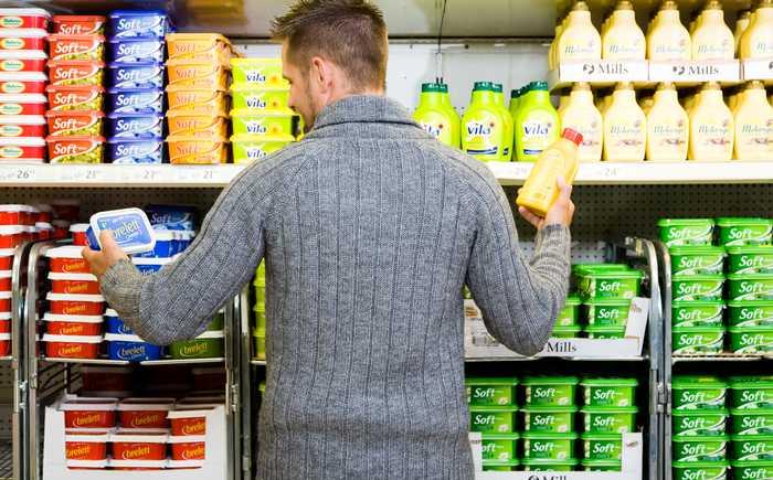 En mann studerer merkingen på to produkter i en butikk.