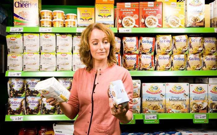 En kvinne studerer merkingen på to pakker frokostblanding i en butikk.