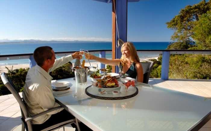 Et par som sitter på en restaurant i solen.