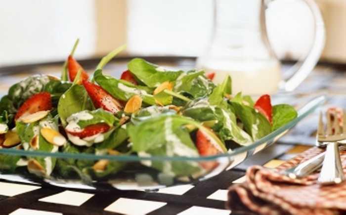 En tallerken med en salat på et bord.