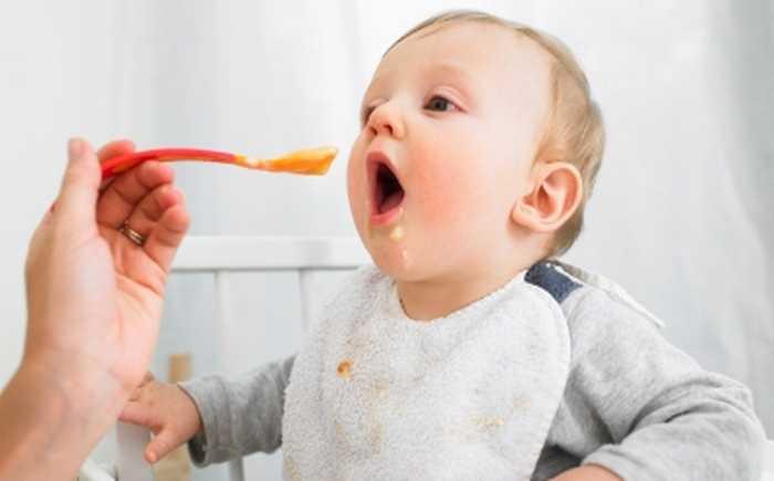 En baby som blir matet av en voksen.