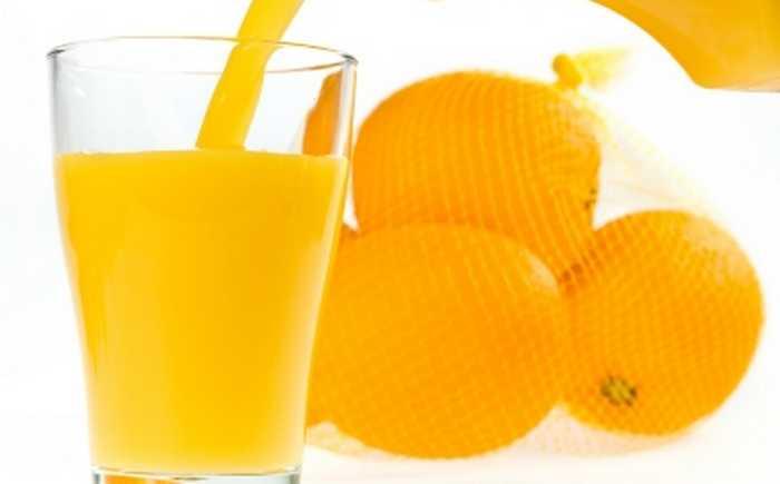 Appelsinjuice som helles i et glass.