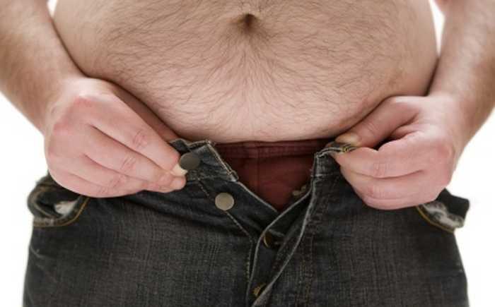En mann med stor mage som forsøker å kneppe knappen i buksene sine.
