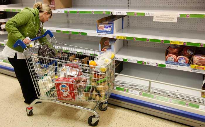 En kunde som handler i en butikk med tomme hyller.