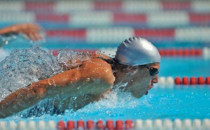 Svømmer med badehette og svømmebriller i basseng.