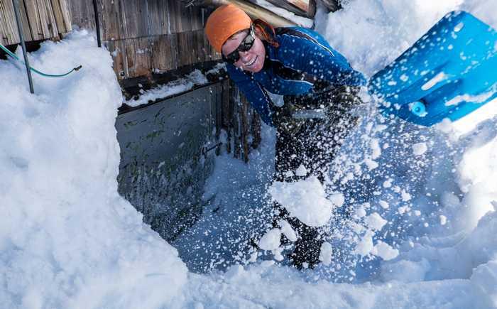 Kvinne som måker snø