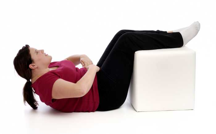 Lett overvektig kvinne som trener sit-ups