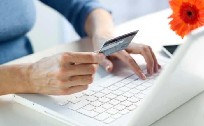 Kvinne som handler via internett med kredittkort