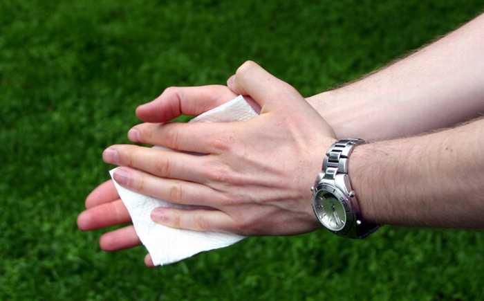 Hender som vasker med hvit serviett