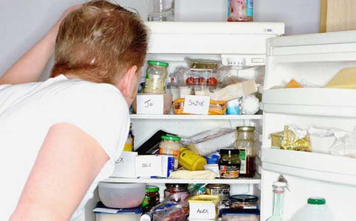 Mann som ser inn i et rotete kjøleskap