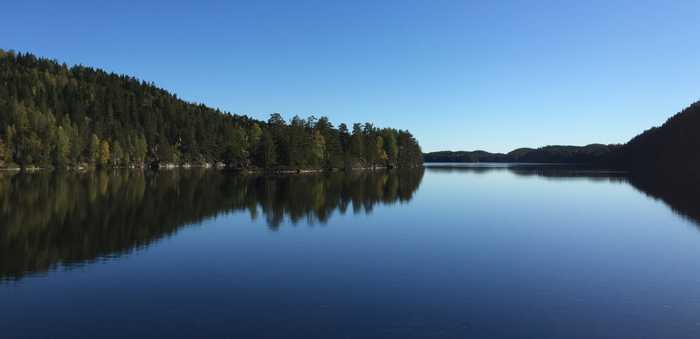Stort vann med skog og åser i bakgrunnen. Nord-Elvåga i Østmarka utenfor Oslo
