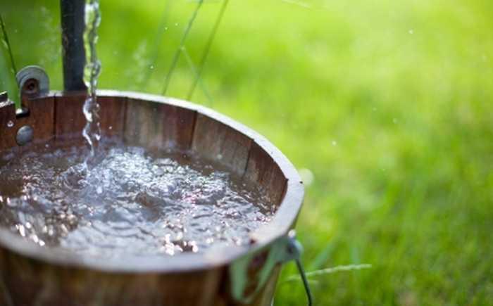 Vann fra kran som renner ned i en trebøtte
