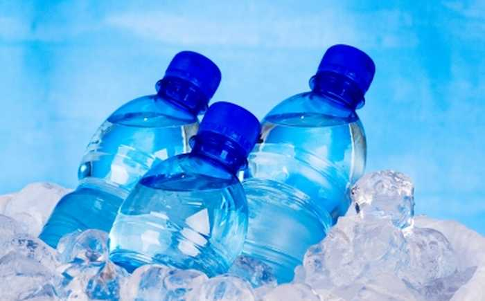Vannflasker med blå kork som ligger i isbiter