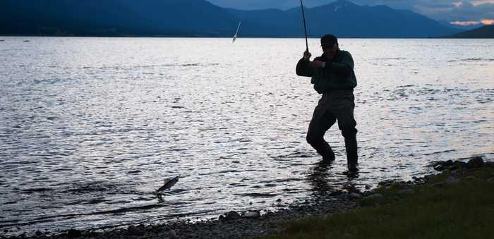En mann som fisker i et vann