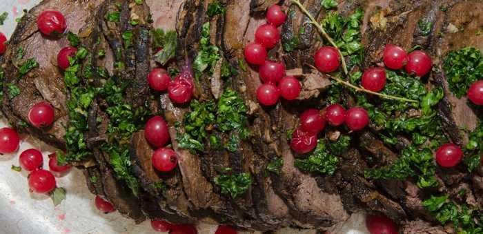 Elkstek med på et serveringsfat med tyttebær og persille