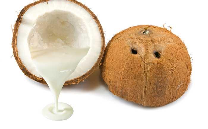 Kokosnøtt delt i to med melk som renner ut