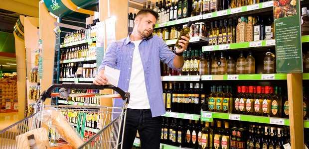 En mann studerer merkingen på en flaske olivenolje i en butikk.