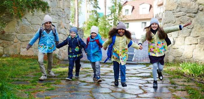 Fem glade små barn som holder hverandre i hendene.