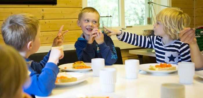 tre gutter i barnehage som spiser fiskemåltid