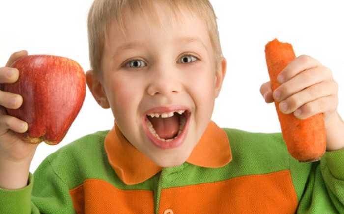 Gutt som holder eple og gulrot i hendene