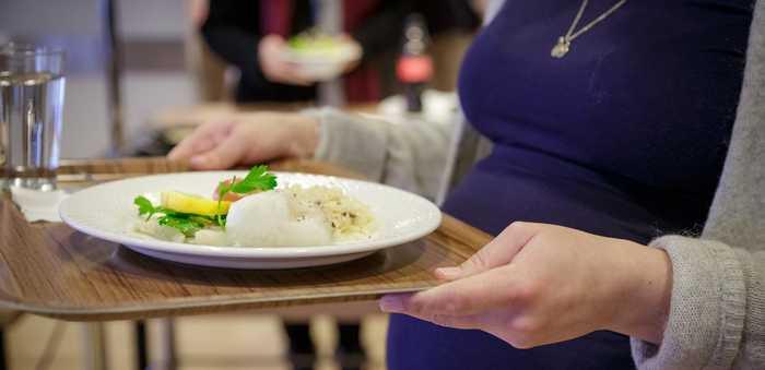 Gravid kvinne som bærer et brett med torskemiddag