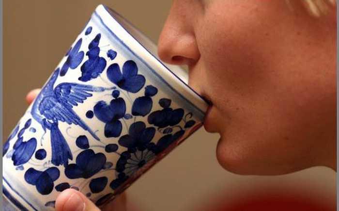En kvinne drikker av en kopp laget av keramikk.